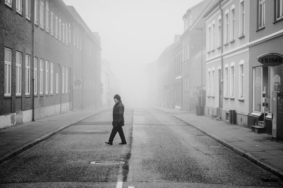 Ældre dame krydser vejen i tågen